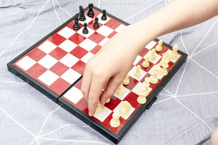 Hand of a child playing chess close up, board games and entertainment concept.