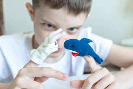 A caucasian boy playing different roles by using finger puppets, toys for expressing his emotions, agression, fear and freandship as a part of psychotherapy. 版權商用圖片