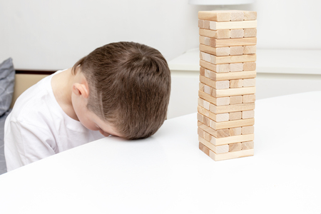 A bored preteen caucasian boy trying to play wooden block tower board game to entertain himself.