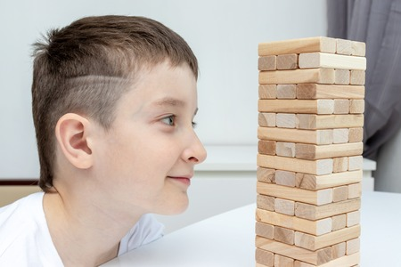 A preteen caucasian boy playing wooden block tower board game for practicing his physical and mental skill and entertainment. Stockfoto