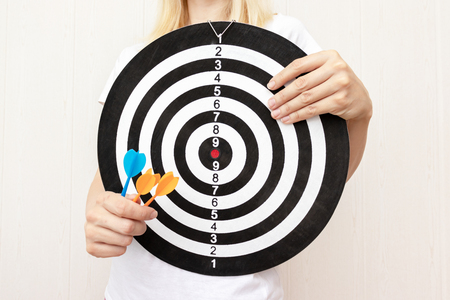 Woman holding a dart board and darts in hands close up, aiming and targetting in business and life concept. 免版税图像