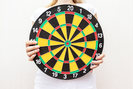 Woman holding a dart board in hands close up, aiming and targetting concept