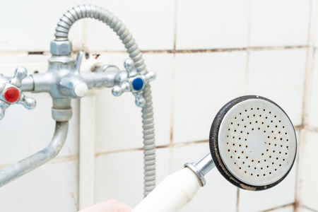 Dirty old shower head close up with limescale and calcified, rusty shower mixer and mould tiles on background, cleaning bathroom concept.
