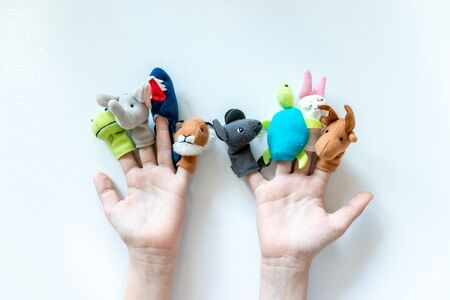 Hands of a child with finger puppets, toys, dolls close up on white background - playing puppet theatre and children entertainment concept. Standard-Bild