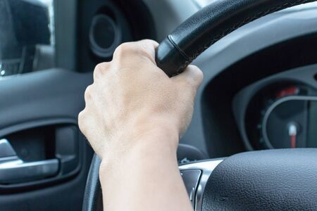 Drivers's hand on a steering wheel of a car while driving.
