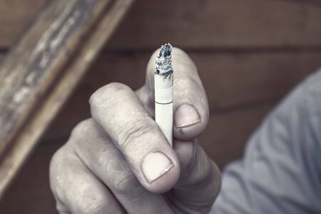 Man holding a lighted cigarette in fingers with a lot of ashes, bad habbits and nicotine addiction concept.