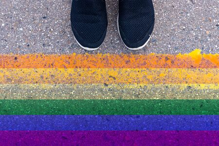 Cropped humans legs in black shoes standing on asphalt in front of lgbt rainbow colored flag, gender identity and self-determination.