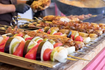 Street food, barbecuing on a hot grill with fire and smoke, vegetables and meat cooked for taking out. Stock Photo - 129863112