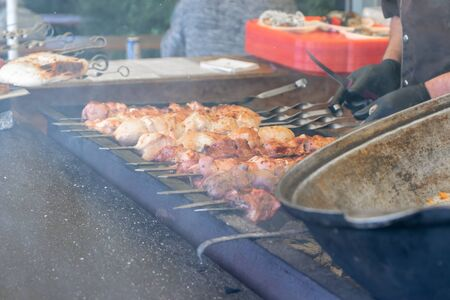 Street food, barbecuing on a hot grill with fire and smoke, vegetables and meat cooked for taking out.