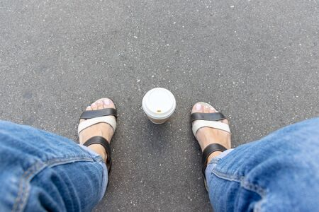 A kraft disposable takeaway paper cup with white cup on asphalt road between woman legs feet wearing leather sandals and jeans, summertime coffee break in city park, copy space.