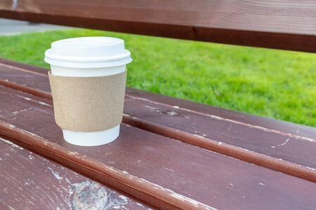 A kraft disposable takeaway paper cup with white cup on a wooden bench and green grass on background in city urban park, summertime coffee break in city park, copy space.