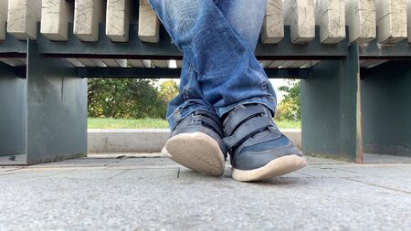 Legs feet of a bored teen boy sitting on a bench in urban city park and wearing jeans and shoes, he is lazy and crossing his legs.