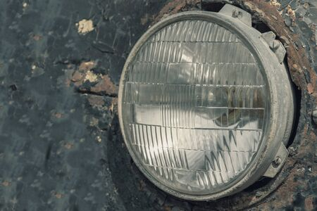 Headlight of an old rusty abandoned car, utilisation and scrap concept.