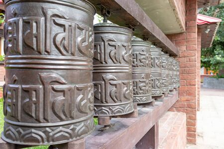 Nepalese traditional metal prayer wheels hanging in a row. 写真素材