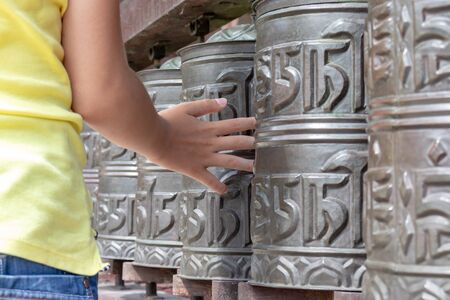 Human hand touching, rotating nepalese traditional metal prayer wheels hanging in a row.
