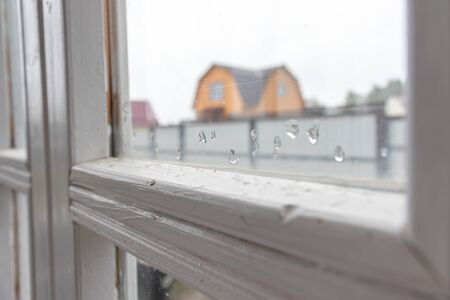 A wooden frame of a window with glass, covered with rain drops in autumn, grey sky and country view outside.