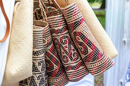 Balinese traditional handmade rattan woven shoulder bags with leather handles at a souvenir street shop. Bali, Indonesia.