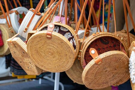 Balinese traditional handmade rattan woven round shoulder bags with leather handles at a souvenir street shop. Bali, Indonesia.