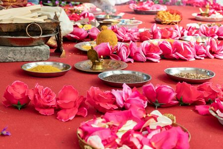 Indian wedding ceremony, decorations for traditional ethnic rituals for marriage, fire burning, flowers and statuettes of the deity on red carpet.