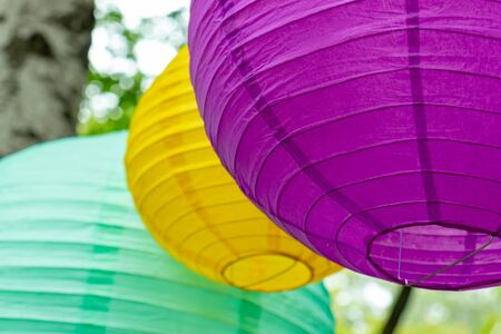 Colorful traditional paper lanterns hanging outdoors, holiday decorations concept.