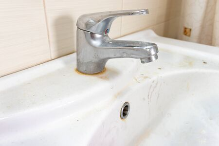 Old dirty washbasin with rust stains, limescale and soap stains in the bathroom with a faucet, water tap.