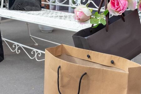 Black and beige paper shopping bags on the ground near the white carven bench with delicate pink flowers.