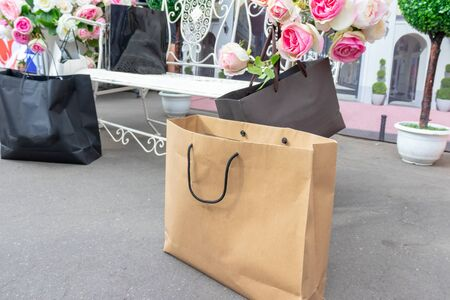 Black and beige paper shopping bags on the ground near the white carven bench with delicate pink flowers. Standard-Bild - 131491811