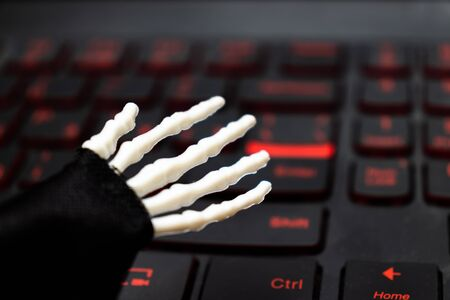 Skeleton hand ready to work on computer, laptop gaming keyboard.