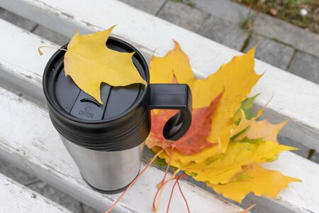 Season, autumn hot drinks and picnic concept - metal thermo coffee cup surrounded by colorful yellow leaves.