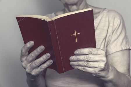 Senior woman holding an old holy bible in hands, Elder woman holding New Testament and praying. Stok Fotoğraf