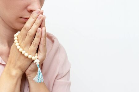 Religeous caucasian young woman praying and holding rosary in hands on white background, copy space.