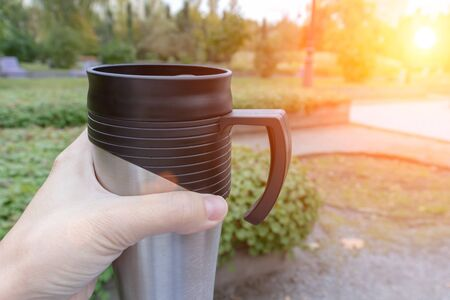 Season, autumn hot drinks and picnic concept - metal thermo coffee cup in woman hand sitting in park, coffee on the go.