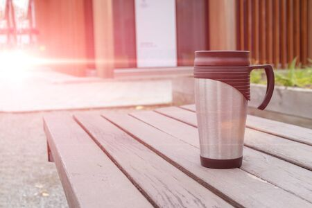 Metal thermo cup with hot drink, tea or coffee on the bench in park copy space, coffee on the go concept. Stok Fotoğraf