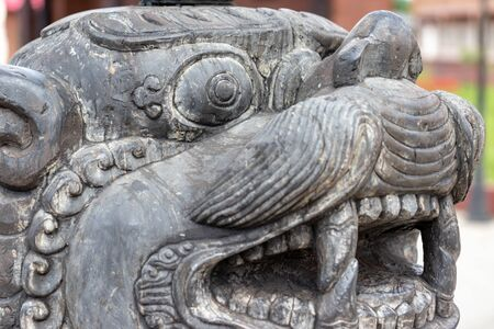 A head of a stone traditional guard lion near the temple in the ethnic centre, close up.