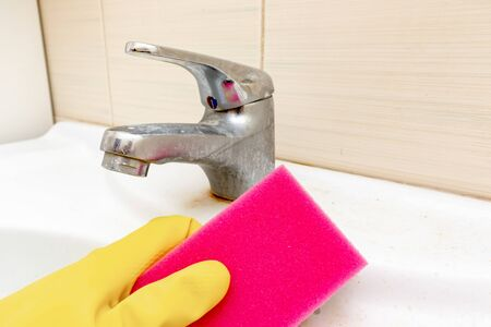 Hand in yellow rubber gloves holding a sponge for washing dirty faucet with limescale, calcified water tap with lime scale on washbowl in bathroom, house cleaning concept. Stockfoto