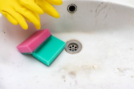 Concept of cleaning old dirty washbasin with rust stains, limescale and soap stains in the bathroom.