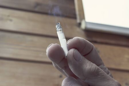 Man holding smoking cigarette in fingers close up, bad habbit and lung cancer concept.