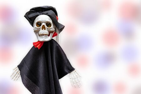Creepy smiling skeleton skull wearing carnival costume for halloween close up on white background with colorful red and blue bokeh with copy space, death and mystery concept, halloween. Stok Fotoğraf