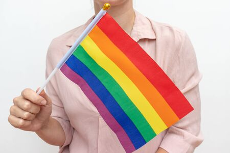 Lesbian woman holding an lgbt rainbow flag in hands as a simbol of freedom and gender equality. Stok Fotoğraf