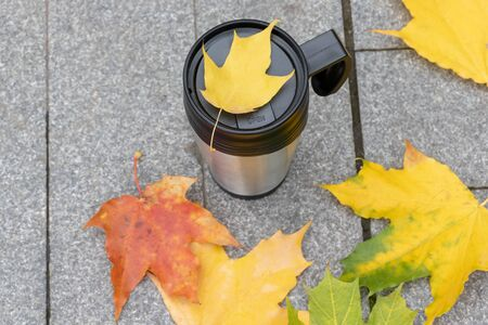 Season, autumn hot drinks and picnic concept - metal thermo coffee cup surrounded by colorful yellow leaves with copy space.