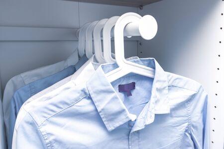 Blaue und weiße klassische Herrenhemden auf Kleiderbügeln in einem Kleiderschrank.