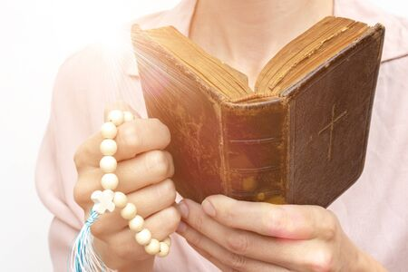 Young praying christian womans hands with a rosary and holy bible . Stok Fotoğraf