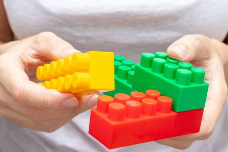Hands of a woman holding colorful toy plastic bricks, blocks for building, playing games and entertainment concept.