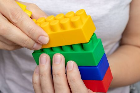 Hands constructing from colorful toy plastic bricks, blocks for building on white background.