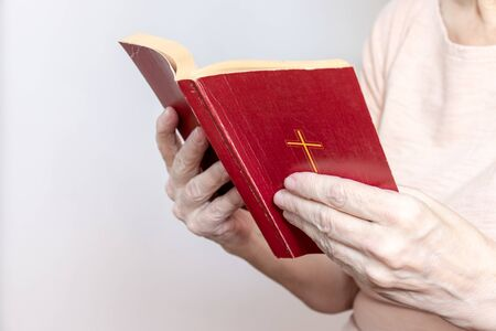 Senior woman holding an old holy bible in hands, Elder woman holding New Testament and praying. Stock Photo