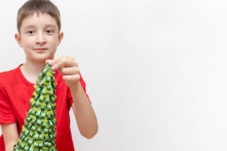 A preteen boy in red t-shirt holding a decorative christmas fir tree on white background with copy space.