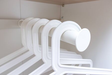 Group of white plastic empty handgers in a wardrobe, hanging on a metal tube.