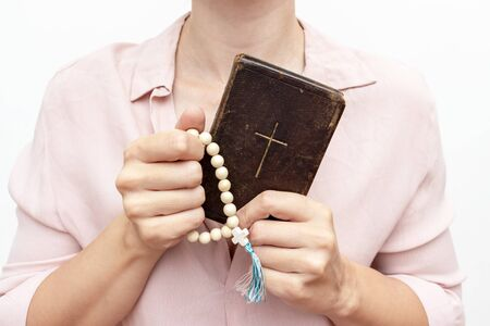 Young praying christian woman's hands with a rosary and holy bible .