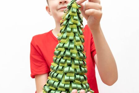A preteen boy in red t-shirt holding a decorative christmas fir tree on white background.