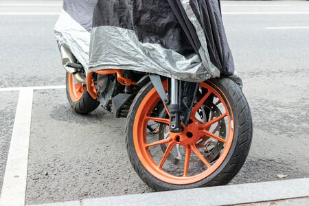 Moscow, Russia - August 02, 2019: Modern motocycle tire thread, wheel parked and covered on a city street.